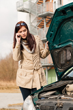 Woman looking under car hood on phone