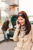 Woman on the phone repairman fixing car