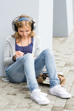 Student teenager writing and listening to music