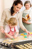 Little girl with mother cutting out cookies