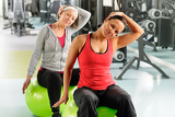 Photo Senior woman with trainer stretching fitness ball