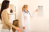 Photo Pediatrician pointing eye-chart at medical office