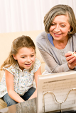 Grandmother teach young girl learn music notes