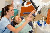 Fényképek Dentist showing child dental procedure on monitor