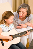 Fotografia Young girl sing play guitar to grandmother