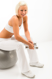 Woman sitting on fitness ball hold dumbbells