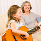 Fotografie Young girl sing play guitar to grandmother