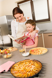 Fotografie Mother and daughter look baking cookbook