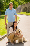 Photo Happy couple with dog on park alley