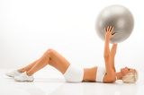 Slim blond woman exercises with fitness ball