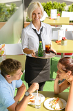 Fotografie Waitress bringing beverages on tray to couple