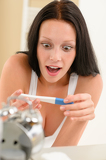 Surprised woman positive pregnancy test result