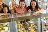 Fotografie Women friends looking at cakes in cafe