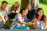 Students relaxing in schoolyard teens meadow park
