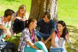 Photo Students sitting in park talking smiling teens