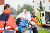 Photo Paramedics with patient on stretcher ambulance aid