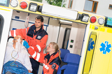 Paramedics checking IV drip patient in ambulance