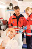 Fotografie Paramedics reading EKG in ambulance patient help