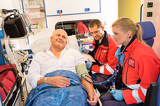 Fotografie Paramedics checking patient pulse in emergency car