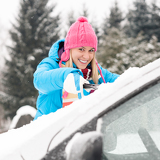 Fotografia Woman cleaning car windshield of snow winter