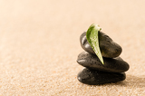 Spa zen stones with leaf on sand