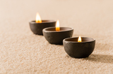 Fotografie Spa therapy three candles on sand
