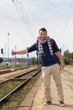 Fotografie Man hitchhiking on railroad train station smiling