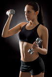 Young fit woman exercise weights on black