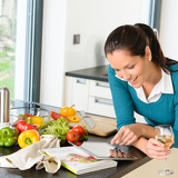 Fotografie Smiling woman searching recipe tablet kitchen vegetables
