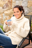 Fotografie Smiling woman drinking tea patio sweater relaxing