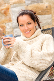 Fotografie Smiling woman drinking hot cocoa relaxing garden