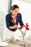 Fotografia Young woman arranging flowers dinner table