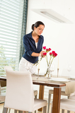 Photo Woman decorating red roses dining room wife
