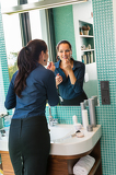 Smiling woman bathroom applying lipstick mirror businesswoman