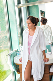 Woman leaning basin bathrobe bathroom thinking morning