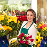 Fotografia Cheerful female florist bouquet roses flower shop