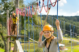 Photo Woman climbing on rope ladder adrenalin park