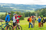 Fotografia Hikers helping cyclists following track nature landscape