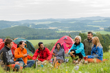 Sitting camping friends with tents and landscape