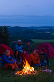 Fényképek In dark camper friends sitting around fire
