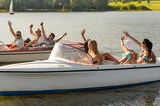 Waving friends sitting in motorboats summertime