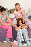 Teenager girls comfort crying friend in bedroom
