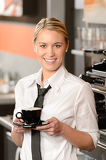 Fotografie Young smiling waitress with cup of coffee