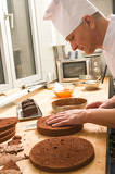Cook in kitchen slicing chocolate cake layers