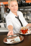Attractive waitress taking tip in bar CZK