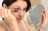 Attractive woman using mascara and handheld mirror