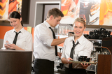 Fotografie Confident waitresses and waiter working in bar