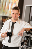 Fotografie Attractive waiter leaning on espresso machine