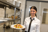 Fotografie Smiling waitress serving salad on plate