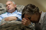 Photo Uneasy senior woman praying for sick man
